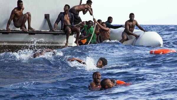 Мигранты с затонувшей лодки возле лодки береговой охраны Ливии во время спасательной операции
