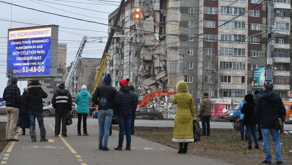 Прохожие наблюдают за ходом работ служб МЧС РФ по расчистке завалов частично обрушившегося жилого панельного дома на Удмуртской улице в Ижевске. Архивное фото