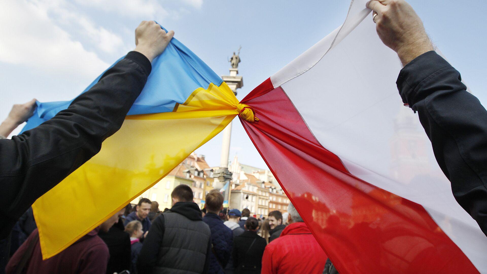 Люди держат связанные флаги Польши и Украины в Варшаве - РИА Новости, 1920, 21.10.2019
