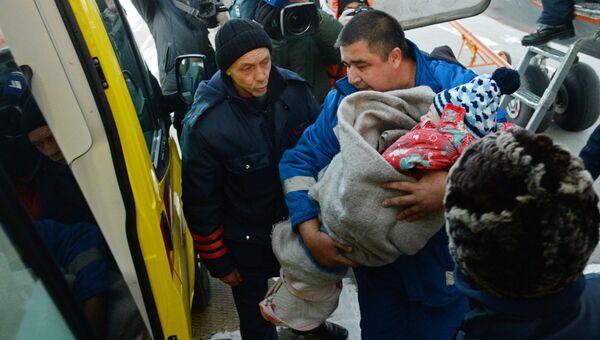 Сотрудник медицинской помощи переносит выжившую при крушении самолета L-410 девочку в автомобиль скорой помощи в Хабаровске. Архивное фото