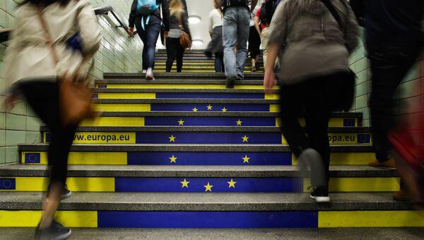 Пассажиры метро поднимаются по лестнице с изображением флага Евросоюза в Берлине