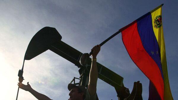 Мужчина с флагом Венесуэлы в Каракасе. Архивное фото