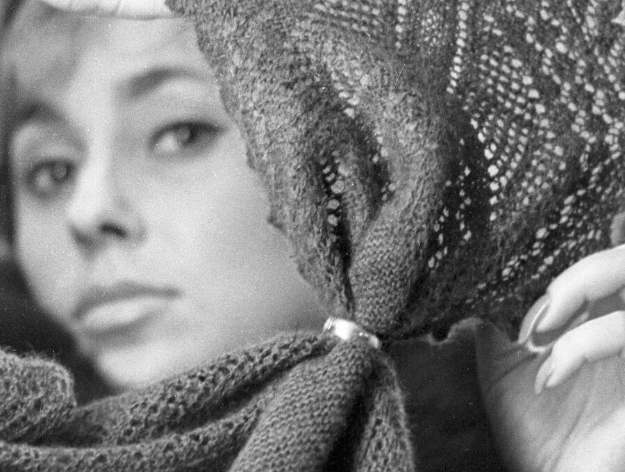 Девушка протягивает оренбургский пуховой платок сквозь золотое кольцо