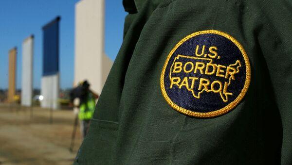 Сотрудник пограничной службы США рядом с прототипами пограничной стены недалеко от границы с Мексикой