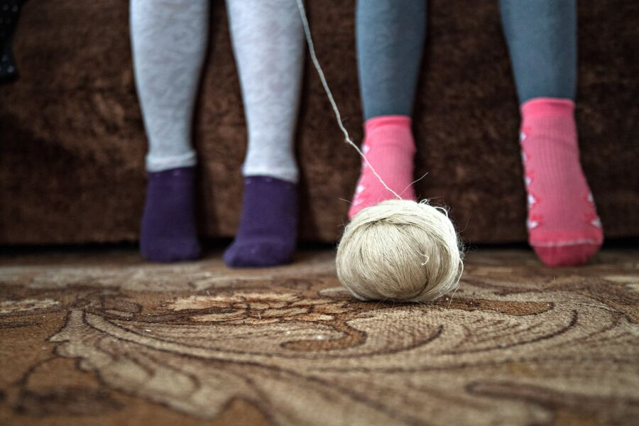 Дети послушно сидят у бабушки и учатся вязать
