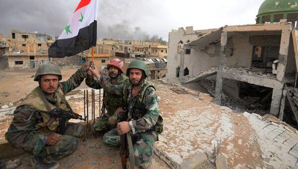 Солдаты сирийской армии с флагом в Пальмире