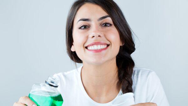 Девушка с ополаскивателем для рта. Архивное фото