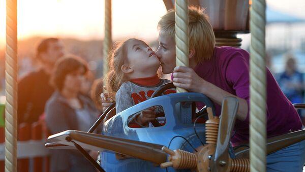 Женщина с девочкой катаются на атракционе. Архивное фото
