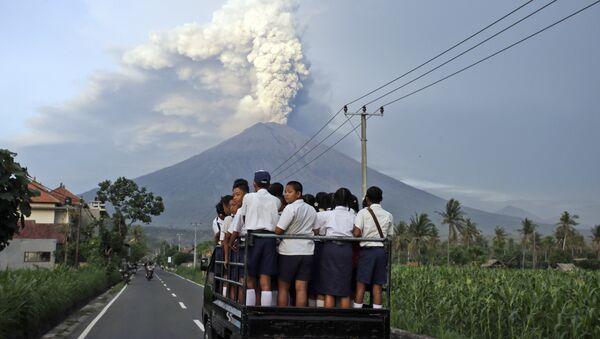 Местные жители по дороге в школу на острове Бали наблюдают за извержением вулкана Агунг, Индонезия. 28 ноября 2017