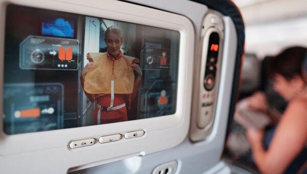 Демонстрация действий при аварии на экране кресла в салоне самолета авиакомпании. Архивное фото