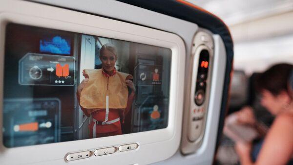Демонстрация действий при аварии на экране кресла в салоне самолета авиакомпании