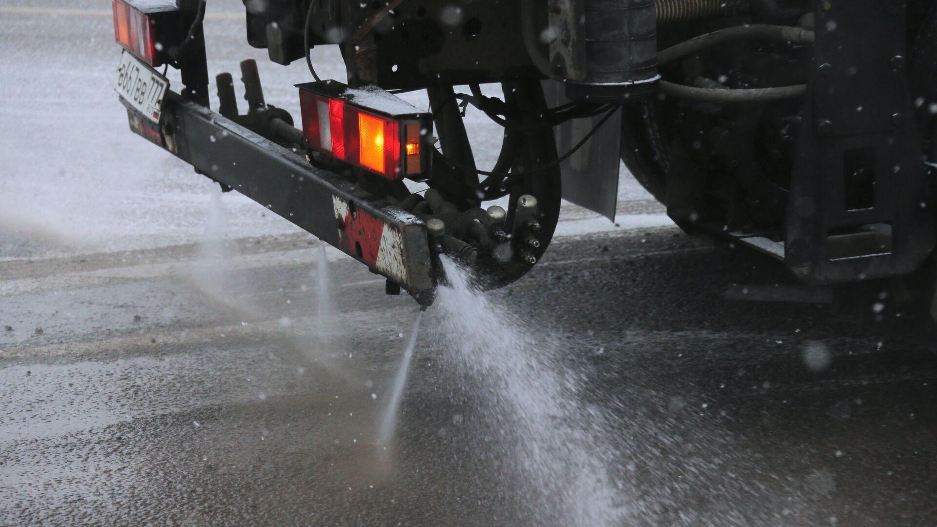 Снегоуборочная машина обрабатывает улицу противогололедным средством в Москве - РИА Новости, 1920, 05.01.2021