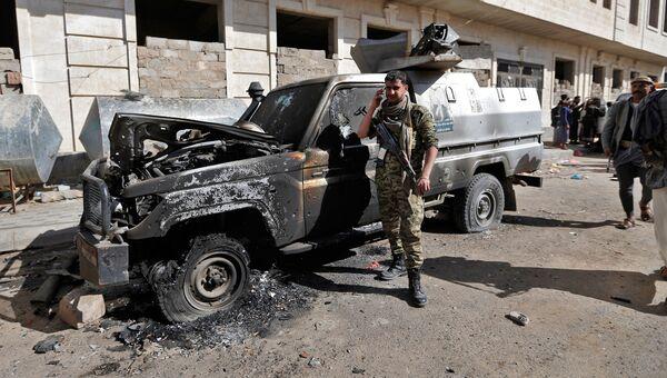 Боевик у сгоревшего бронированного автомобиля недалеко от резиденции президента Йемена Али Абдаллы Салеха в Сане