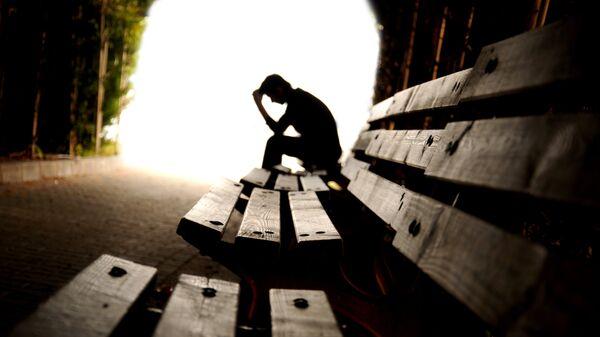 Молодой человек на скамейке. Архивное фото