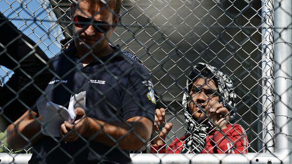 Полицейский в лагере беженцев с Ближнего Востока на острове Лесбос в Греции