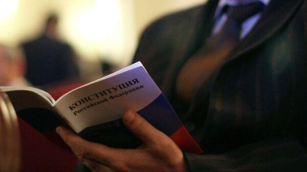 Мужчина с Конституцией РФ в руках