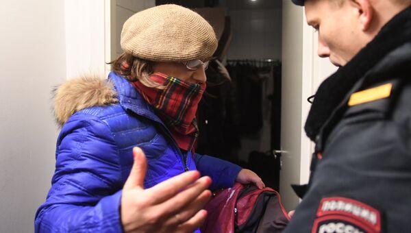 Сотрудник полиции досматривает мужчину в женской одежде, облившего фотографии на выставке Без смущения американского фотографа Джока Стерджеса в Центре фотографии имени братьев Люмьер