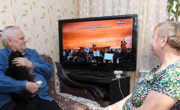 Семья пенсионеров в Казани смотрит по телевизору трансляцию пресс-конференции президента РФ Владимира Путина