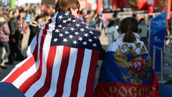 Молодые люди в национальных флагах США и России. Архивное фото