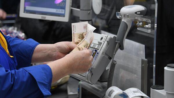 Кассир считает деньги. Архивное фото