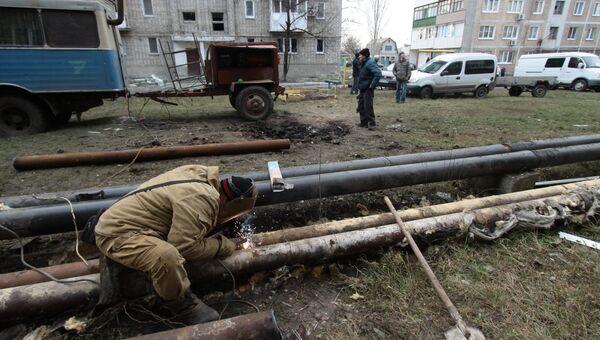 Сотрудник ЖКХ ремонтирует трубы жилого дома