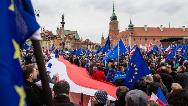 Люди с флагами Польши и ЕС в Варшаве