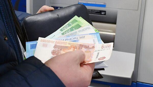 Снятие денег в банковском терминале в Москве. Архивное фото