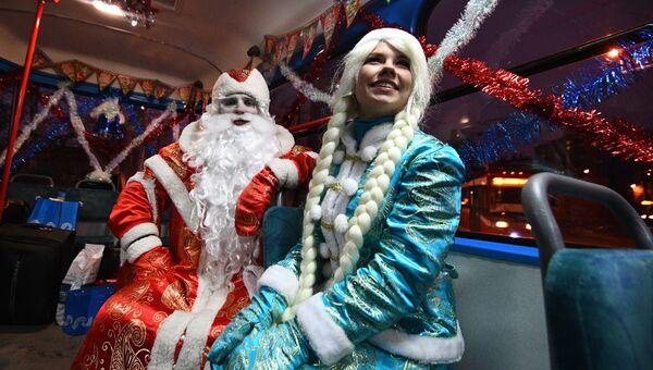 Дед мороз и Снегурочка в салоне новогоднего трамвая, украшенный яркими светодиодными огнями, в Москве