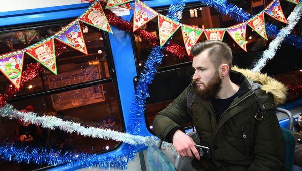 Пассажир в салоне новогоднего трамвая, украшенный яркими светодиодными огнями, в Москве