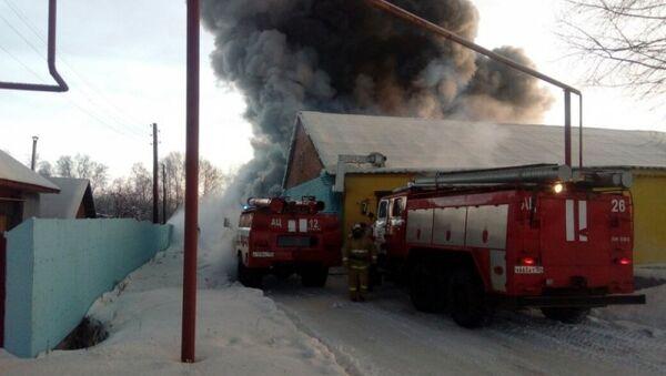 Автомобили пожарной службы МЧС РФ во время тушения пожара в здании с обувным производством в поселке Чернореченский Искитимского района Новосибирской области. 4 января 2018
