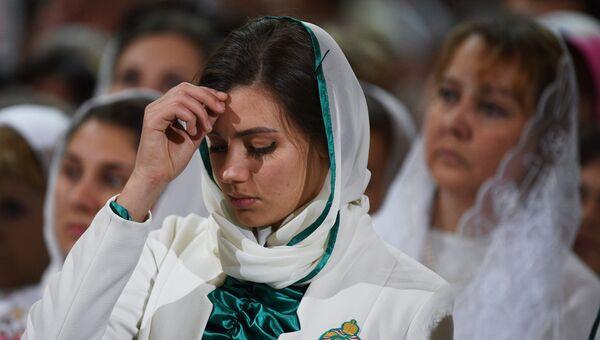 Девушка-волонтер в храме Христа Спасителя во время Рождественского богослужения