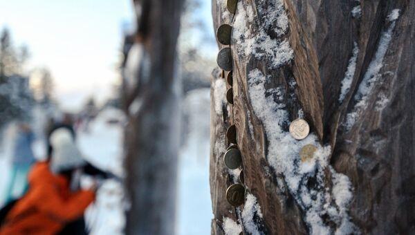 Китайские туристы оставляют монетки у деревянных идолов в саамской деревне Самь-Сыйт в поселке Ловозеро Мурманской области. Архивное фото