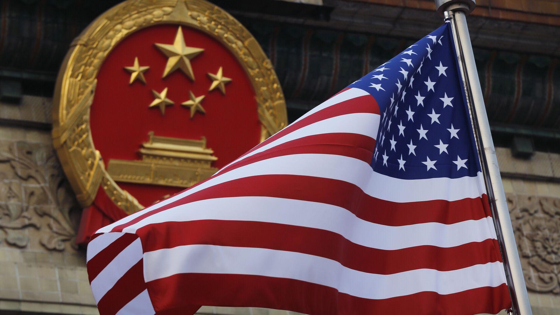 Флаг США на фоне эмблемы Китая в Пекине - РИА Новости, 1920, 03.03.2021