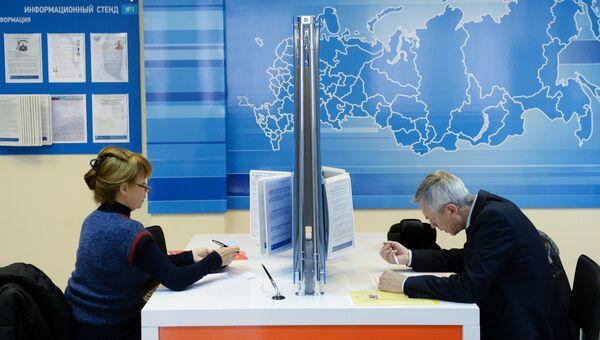 Посетители заполняют документы в инспекции Федеральной налоговой службы РФ. Архивное фото