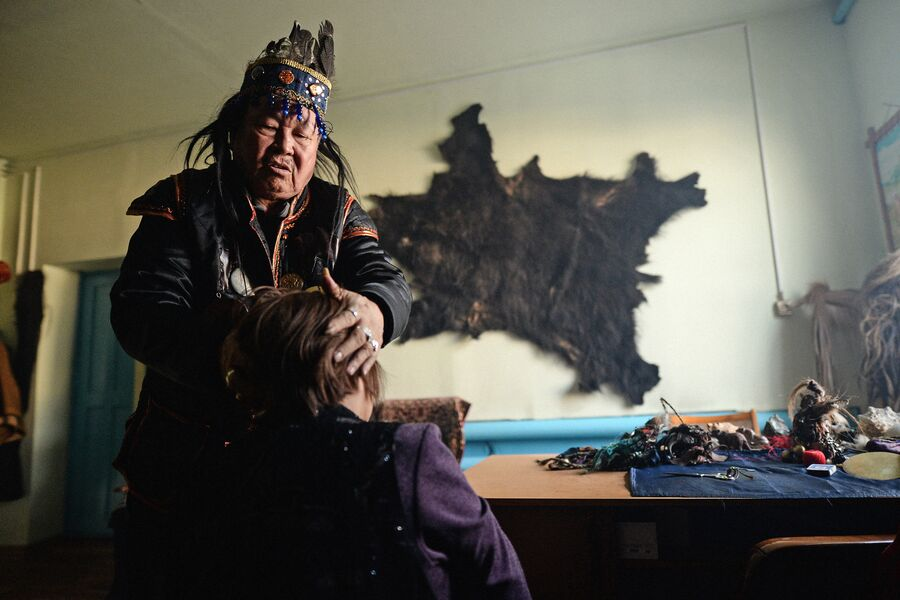 Председатель шаманского общества Адыг-Ээрен (Дух медведя), верховный шаман Республики Тыва Допчун-Оол Кара-оол Тюлюшевич проводит обряд с посетителем в своей комнате в доме, который занимает шаманское общество в Кызыле