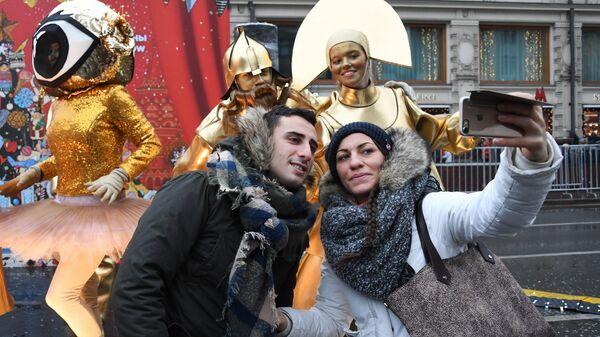 Посетители фотографируются с участниками анимационной программы на фестивале Путешествие в Рождество на Тверской улице в Москве