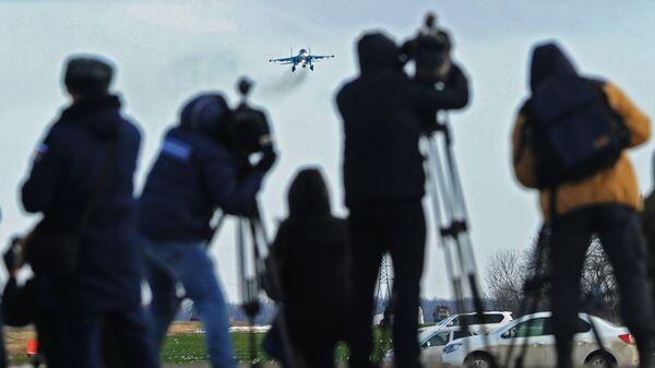 Журналисты наблюдают за посадкой на автотрассу в Ростовской области истребителя-бомбардировщика Су-34