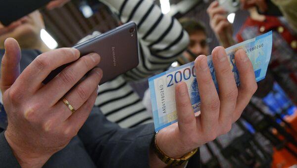 Мужчина сканирует купюру телефоном, на котором установлено новое мобильное приложение АО Гознак - Банкноты 2017