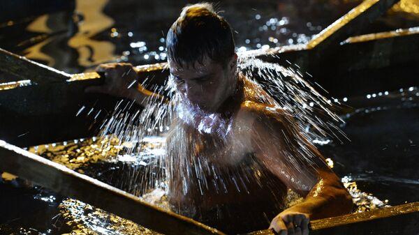 Мужчина во время крещенского купания в озере Соловей-Ключ Надеждинского района Приморского края