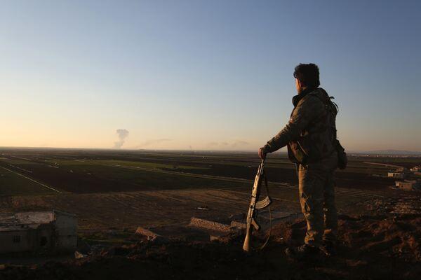 Сирийский боец наблюдает за районом Африна