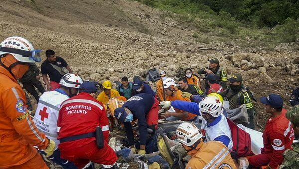 Спасатели ищут тела пассажиров автобуса, который попал под оползень на дороге между Хунина и Тукерреса в Колумбии. 21 января 2018