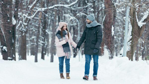 Молодая пара во время прогулки в парке зимой. Архивное фото