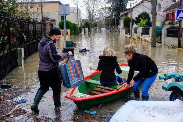 Местные жители переправляются на лодке на одной из затопленных улиц в Париже, из-за прошедших ливневых дождей