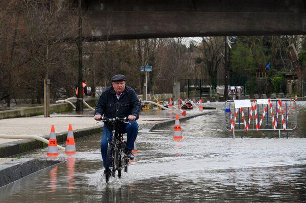 Местный житель едет на велосипеде по одной из затопленных улиц в Париже, из-за прошедших ливневых дождей.