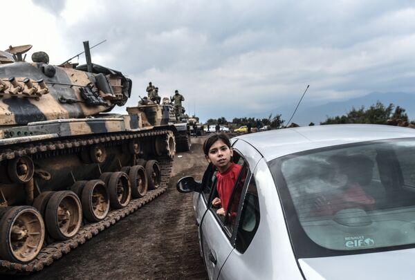 Турецкая девочка выглядывает из окна автомобиля во время стягивания войск турецкой армии к границе с Сирией
