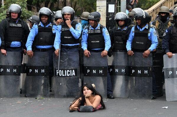 Девушка лежит на асфальте во время протеста против переизбрания на посту президента Хуана Орландо Эрнандеса в Гондурасе