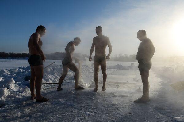 Спортсмены клуба закаливания и зимнего плавания во время купания в проруби на озере в Ленинском районе Новосибирска