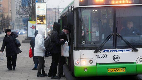 Пассажиры садятся в автобус на одной из улиц в Москве. Архивное фото