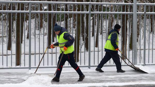 Дворники убирают снег с платформы одной из железнодорожных станций