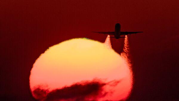 Самолет Airbus A-321 на фоне закатного солнца